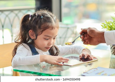 The girl kept playing the tablet. By not interested to eat the food fed by her father