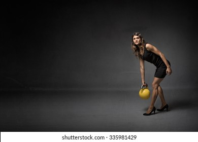 girl with kettlebell and high heels, dark background