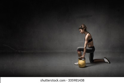 girl with kettlebell on hand, dark background