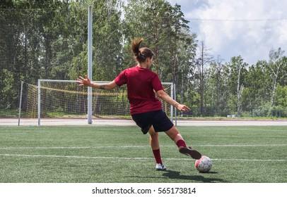 Girl kick the ball at the football stadium