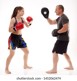 Girl kickboxing fighter hitting mitts with her coach, isolated on white background