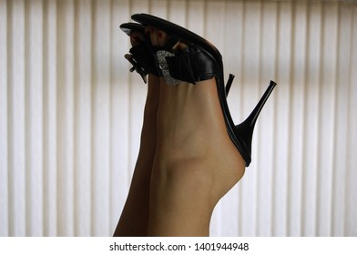 Girl kicks her sexy high heels in the air. Office window background (closeup)