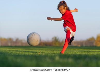Mädchen tritt einen Fußball auf dem Fußballfeld