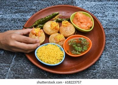 Girl / kid / boy taking spicy Pani puri golgappe with hand, Chat item, India. Indian panipuri snacks eaten with tangy tamarind water, potato stuffing, North Indian street food Delhi, Mumbai, Rajasthan