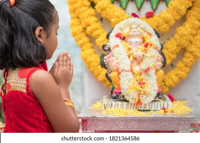 Girl Kid praying by closing eyes and folding hands in front of Lord Ganesha Idol during Ganesha or vinayaka Chaturthi festival ceremony at home - concept of Indian religious festival celebrations