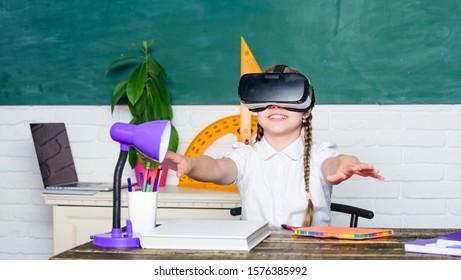 Girl kid study in virtual school. Virtual education. Child cute pupil wear hmd vr glasses. Virtual teaching. Studying in virtual reality. Modern technology. Interesting lesson. Homeschooling online.