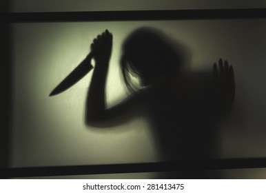 Girl killer with a knife in her hand. Shadowy figure behind glass