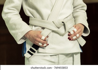 A girl in a kimono kneads before training in judo and jujitsu