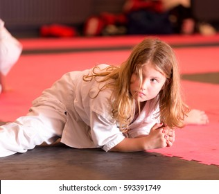 Girl in kimono; young girl in a white kimono; Healthy young girl in karate sports school