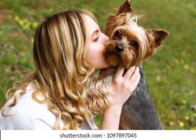 The girl kisses the beloved Yorkshire terrier