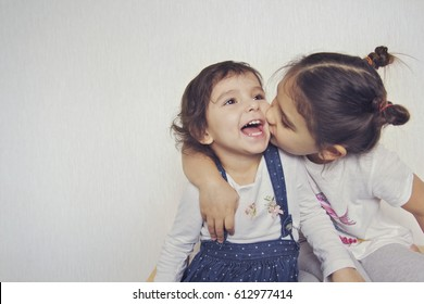 The girl kisses her sister on a white background