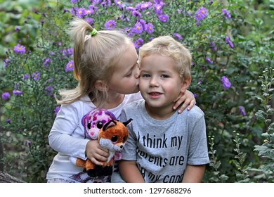 Girl Kissing a Boy on a Background of Flowers