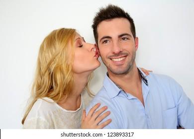 Girl kissing boyfriend on white background