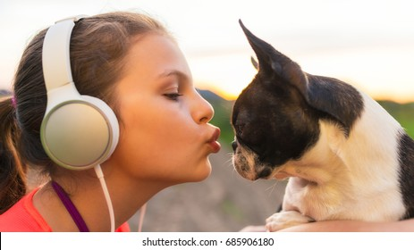 Girl kissing her dog - boston terrier - and listening to music