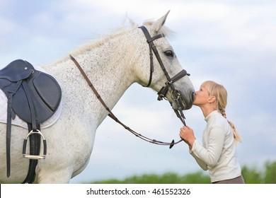 Girl kissing a horse.