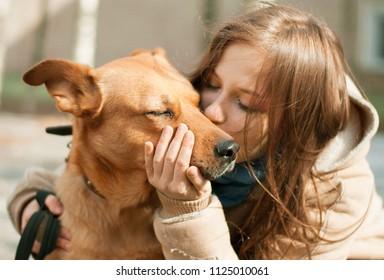 Girl kissing hugging dog pet cute adorable red dog friendly closeup closing eyes funny animals
