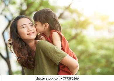 Girl kissing mother when she giving her piggyback ride