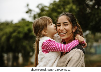 Girl kissing on the cheek of her nanny at the park. Babysitter having fun with a girl at the park.