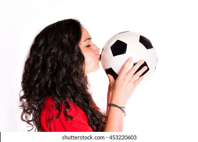 Girl kissing soccer ball isolated background