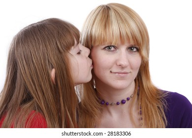 Girl is kissing woman. Daughter's kiss. Daughter kissing her happy mother.  Isolated on white in studio.