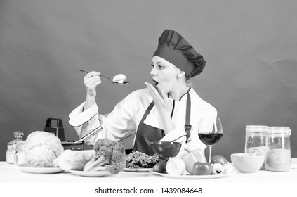 Girl at kitchen table. Cooking food and housekeeping. Housewife routine. Professional cooking tips. Woman chef try taste eat food. Delicious recipe concept. Cooking meal. Cooking healthy food.