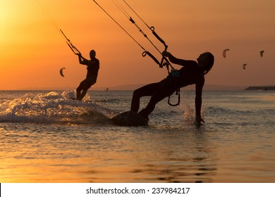 Girl kiter riding on a beautiful background of spray and colourful sunset of Black sea