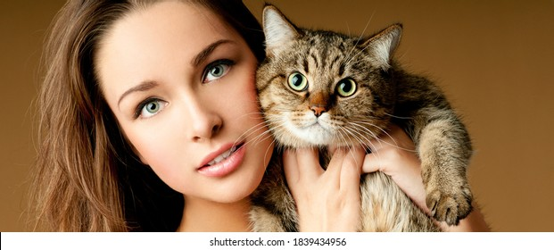Girl with a kitten. Young woman holding cute cat. Adorable domestic pet concept.