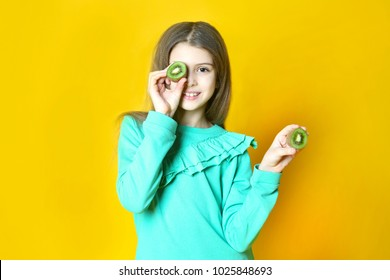 the girl with kiwi fruit on a yellow background