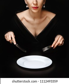 girl with knife and fork in hands in black dress holds over white plate on black table