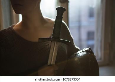 girl knight in armor holds sword and helmet
