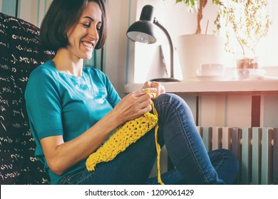 Girl knits crochet at home. Woman engaged in needlework. A knitter sits on a sofa and works. Creative hobby. Training patience and perseverance. Crochet thick yarn.