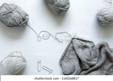 Girl knits gray sweater knitting needles on gray wooden background. Process of knitting. Top view. Flay lay