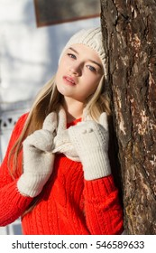 Girl in a knitted cap and mittens standing, leaning against a tree