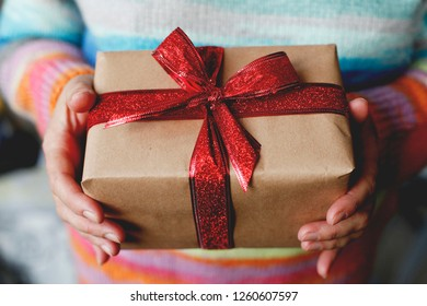 The girl in a knitted color sweater holds a New Year's gift. Christmas holidays