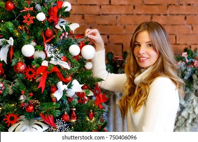 Girl in knitted jumper decorates the Christmas tree in the loft room