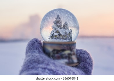Girl in knitted mittens holding glass ball with firtrees, house and artificial snow falling inside the ball with winter landscape at the  background