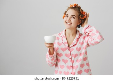 Girl knows she will be fabulous at party. Indoor shot of attractive female student at dormitory, wearing hair curlers while making hairstyle, standing in nightwear, drinking cup of coffee