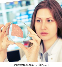 girl in the laboratory of food quality tests sausage
