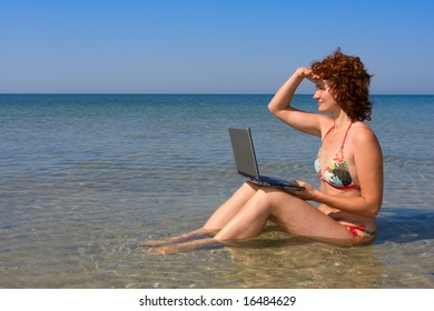 Girl with laptop computer sitting in a sea