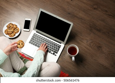 Girl with laptop and food relaxing on floor