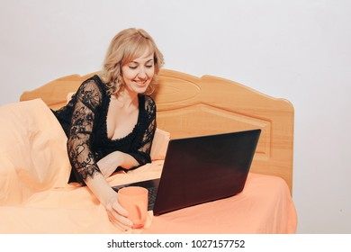 Girl with laptop lies in bed