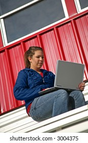 girl with laptop on the bleachers