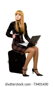 Girl with laptop sitting on a suitcase