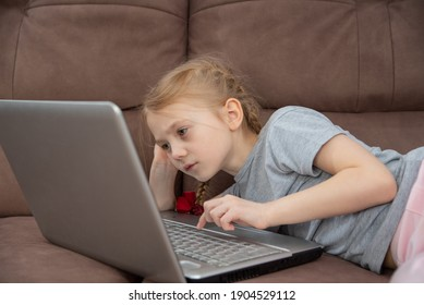 the girl at the laptop is undergoing online training, children are taught on distance courses at home, the child lies on the brown sofa and looks at the computer