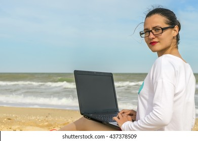 Girl with a laptop working on the sea beach