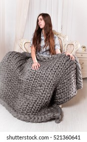 Girl with large grey knit blanket , giant knit blanket, super chunky yarn, arm knitting