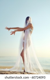 A girl in a large white veil dancing on the beach. Artistic colors added. Vertical photo