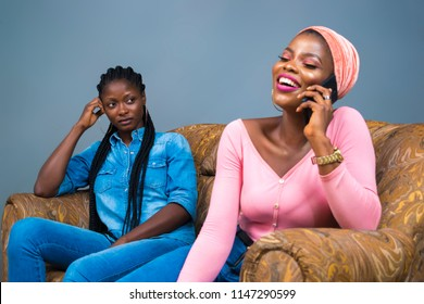 a girl laughing and making a phone call while another girl behind her is staring at her angrily and jealously