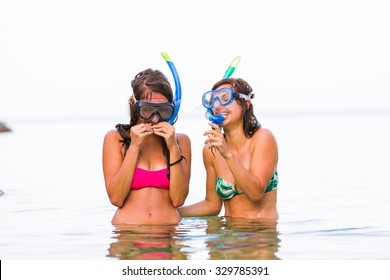 Girl laughing on the funny looks of her friend with snorkeling goggles and pipe.