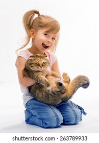 Girl laughs loudly. Hugging cat. She is happy.